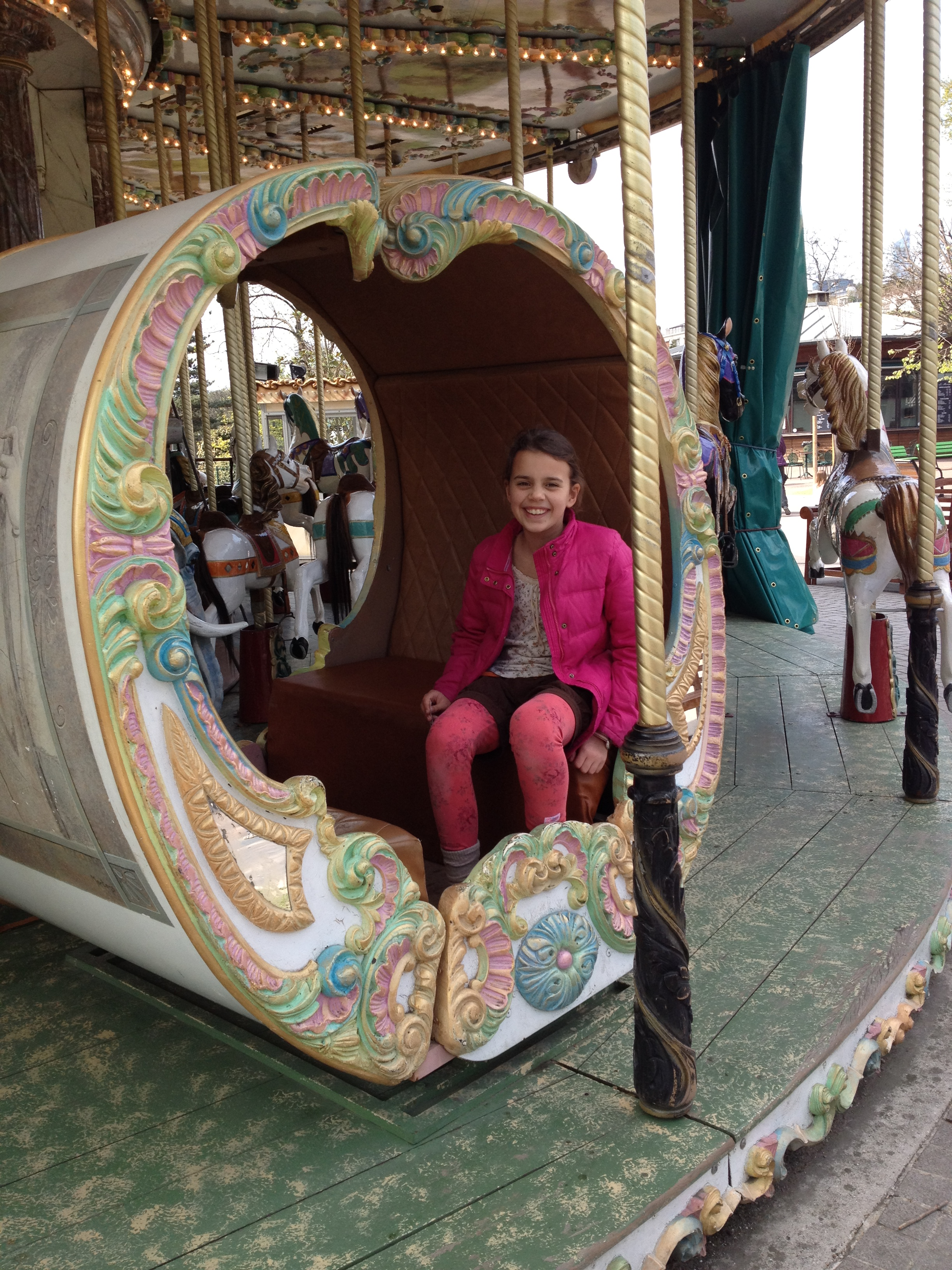 Young girl in carriage on carousel in Jardin d'Acclimatation