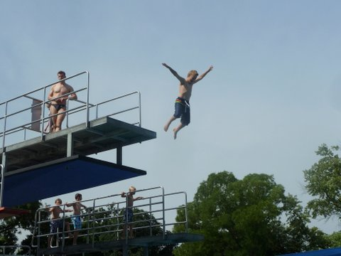 Little boy flying through air after jumping off 5m diving board