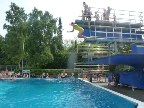 middle-aged woman jumping off 3m diving board