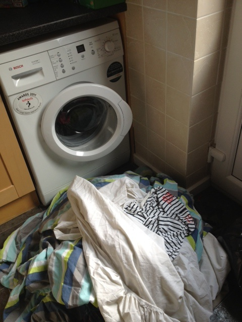 A pile of dirty washing in front of a washing machine